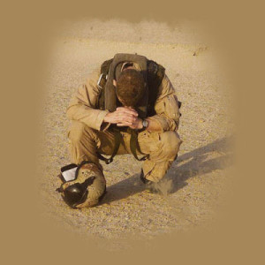 soldier praying in sand