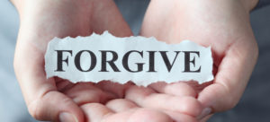 "Torn piece of paper with the word ""Forgive"" in the woman's palms."